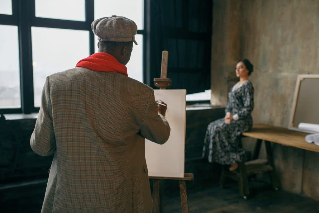 Portrait painter with brush draws female model
